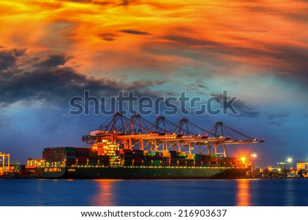 Container Cargo freight ship with working crane bridge in shipyard at dusk. - stock photo