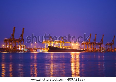 Container Cargo freight ship with working crane bridge in shipyard at dusk for Logistic Import Export background. - stock photo
