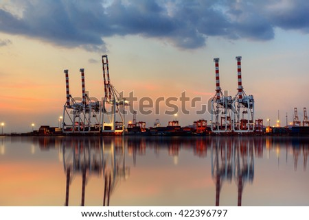 Container Cargo freight ship with working crane bridge in shipyard at dusk for Logistic Import Export background - stock photo