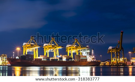 Container Cargo freight ship with working crane loading bridge in shipyard at dusk for Logistic Import Export backgroun - stock photo