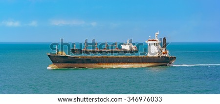 Container cargo ship and oil tanker passes Strait of Singapore - stock photo
