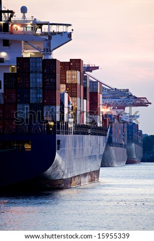 container cargo ships docked in port - three huge freighters at harbor terminal during sunset - stock photo