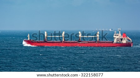 Container freighter ship sailing in stormy ocean - stock photo