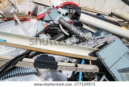 container full of pipes and pieces of plastic and other trash specials - stock photo