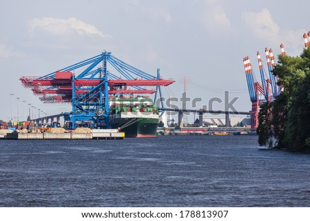 Container harbor with tall cranes in Hamburg Harbor, Germany - stock photo