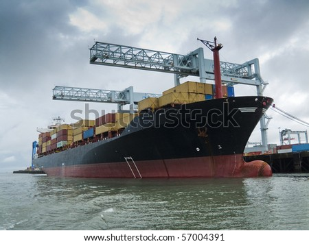 Container ship being loaded in harbor - stock photo
