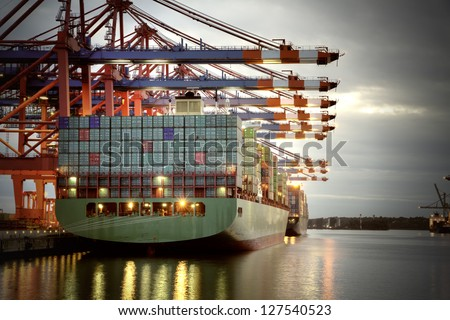 Container ship in the harbor of Hamburg, night shot. Cloudy sky. - stock photo