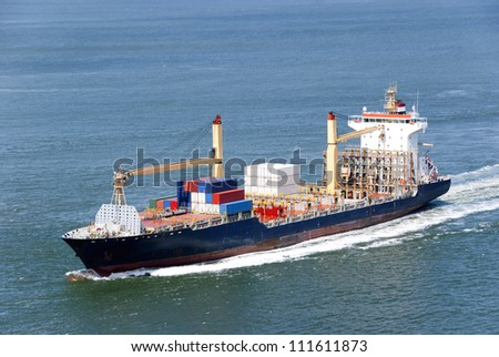 Container Ship travelling to a harbor far away where it will unload its fright - stock photo