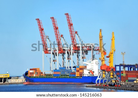 Container stack and ship under crane bridge - stock photo