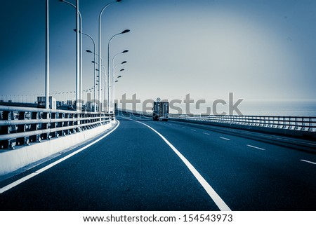 container truck on the cross-sea bridge in shanghai - stock photo