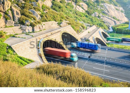 container trucks motion blur and highway tunnel in morning - stock photo