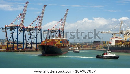 container vessel and a small ship, no logos on the photo leaving the port of Durban South Africa - stock photo