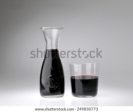 container with glass of red wine - stock photo