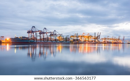 Containers loading Shipping by crane at dark or Trade Port - stock photo