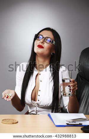 Contemplating Business Woman With Pills And Glass Of Water At Desk In Office - stock photo