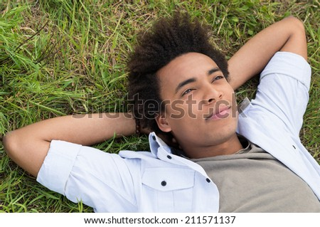 Contemplating Young African Man Lying On Grass - stock photo