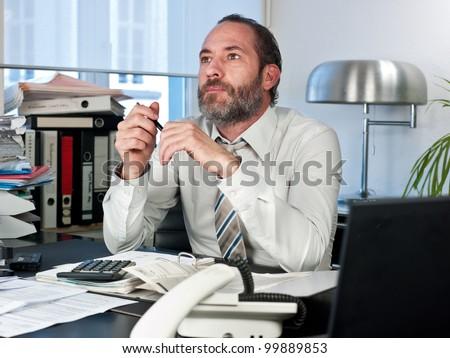 Contemplative businessman looking away at work. Horizontal shot - stock photo