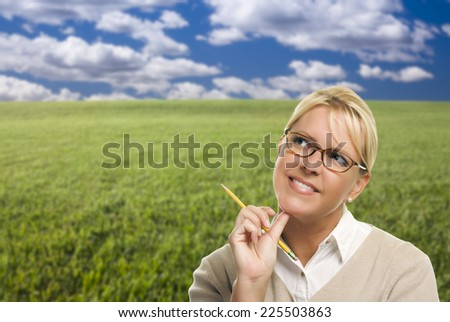 Contemplative Woman in Grass Field Looking Up and Over to the Side. - stock photo