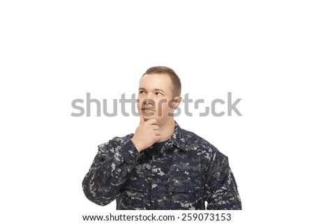 Contemplative young man in navy uniform with hand on chin - stock photo