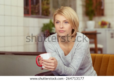 Contemplative young woman drinking coffee clutching a mug on her hands as she stares ahead of her with a serious distracted expression, with copyspace indoors at home - stock photo