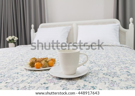 contemporary and classic bedroom with tea cup and cape gooseberry. - stock photo