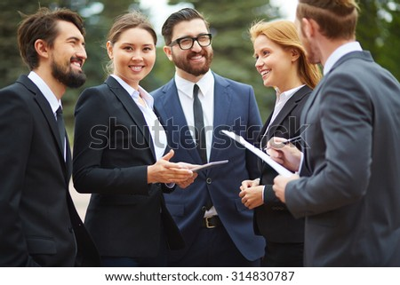 Contemporary businesswoman with touchpad looking at camera during outdoor meeting with partners - stock photo