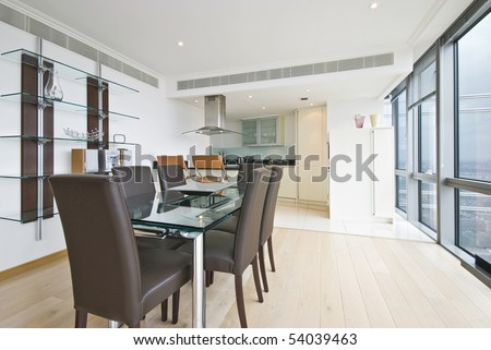 Contemporary designer interior of dining area and kitchen with large dining table and leather chairs for six - stock photo