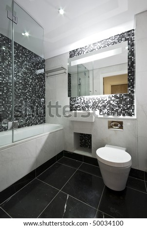 Contemporary en-suite bathroom in black and white with white ceramic bath tub, wash basin and toilet with mosaic tiled walls and marble fragments - stock photo