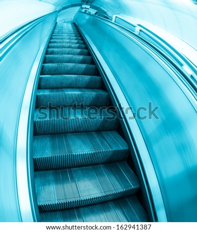 Contemporary escalator stairs. Fisheye view, blue toned - stock photo