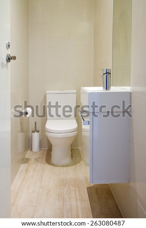 Contemporary fully tiled powder room toilet in a new renovated home - stock photo