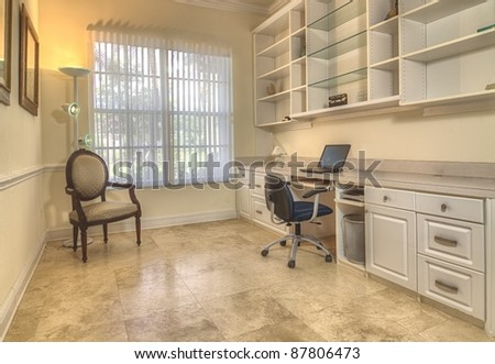 Contemporary home office with book cabinets, shelves, and workspace - stock photo