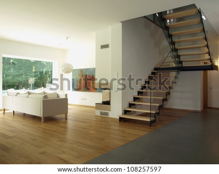Contemporary house: staircase and a living room - stock photo