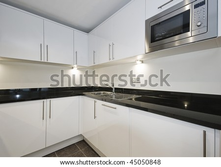 contemporary kitchen unit with black granite worktop and built-in appliances - stock photo