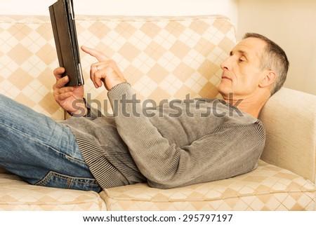 Contemporary mature man using digital tablet indoors. - stock photo