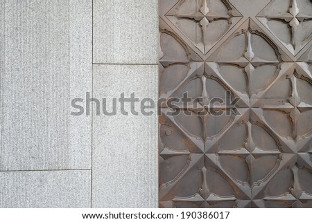 contemporary pattern on wooden door and stone wall - stock photo
