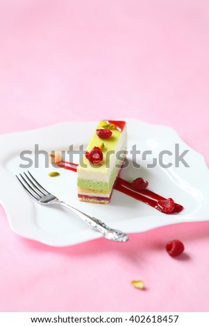 Contemporary Plated Dessert. Piece of Pistachio, Raspberry Mousse Cake on a square white plate, on a light pink background. - stock photo