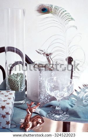 Contemporary style Christmas decor - ceramic reindeer and champagne glasses on coffee table in bright light from the window. Natural light. Toned photo. Shallow focus on the silver reindeer. - stock photo