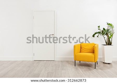 Contemporary waiting room with a yellow armchair and a plant in a white flowerpot behind it - stock photo