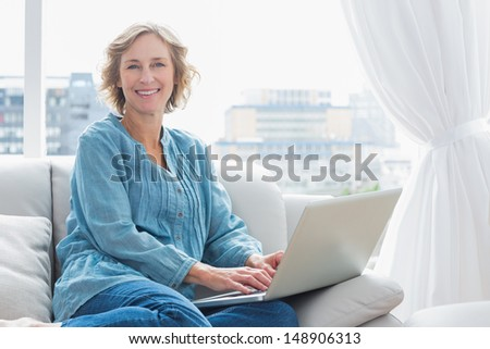 Content blonde woman sitting on her couch using laptop smiling at camera at home in the sitting room - stock photo