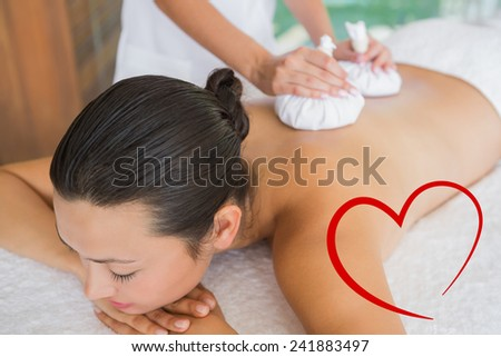 Content brunette getting a herbal compress massage against heart - stock photo