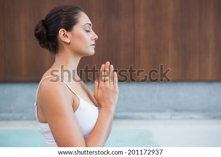 Content brunette in white sitting in lotus pose in health spa - stock photo