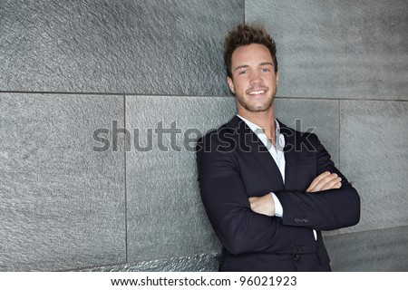 Content business man leaning on wall with his arms crossed - stock photo