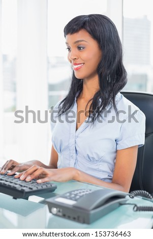 Content businesswoman typing on a keyboard in office - stock photo