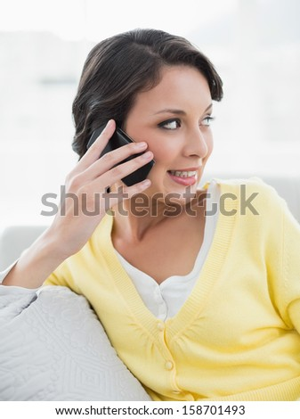 Content casual brunette in yellow cardigan calling with her mobile phone sitting on a couch in bright living room - stock photo