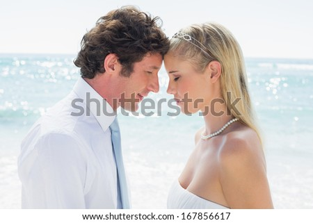 Content couple embracing each other on their wedding day at the beach - stock photo