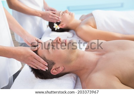 Content couple enjoying head massages poolside outside at the spa - stock photo