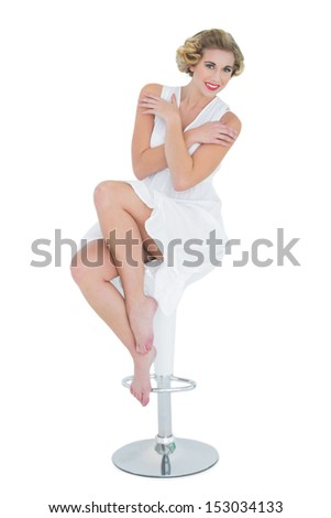 Content fashion blonde model posing sitting on bar chair on white background - stock photo