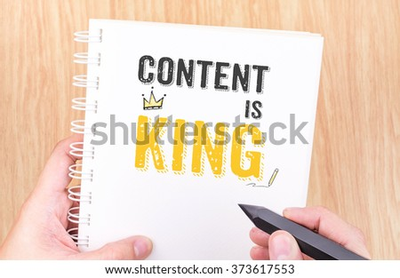 Content is King work on white ring binder notebook with hand holding pencil on wood table,Digital Business concept - stock photo