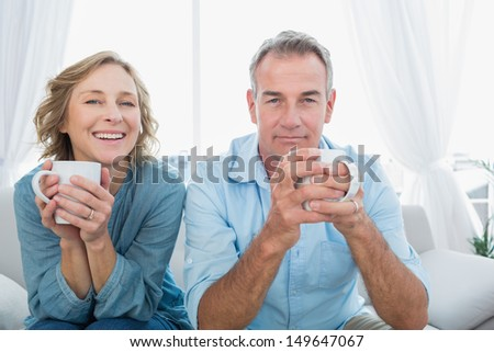 Content middle aged couple sitting on the couch having coffee smiling at camera at home in the living room - stock photo