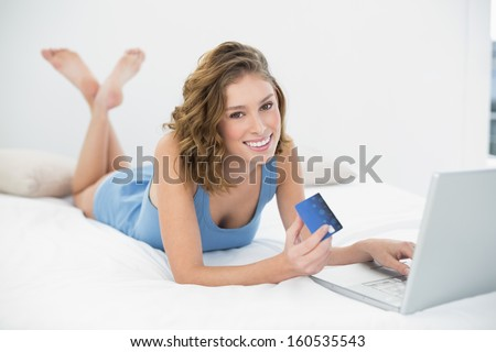 Content peaceful woman home shopping with notebook lying on her bed smiling at camera - stock photo